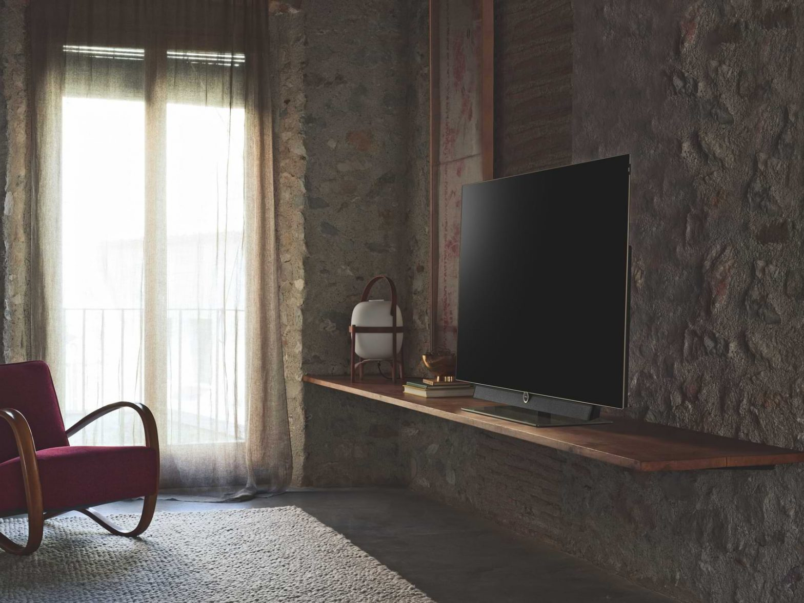 A 4K TV sits on a stand in an empty room as the light reflects off of it