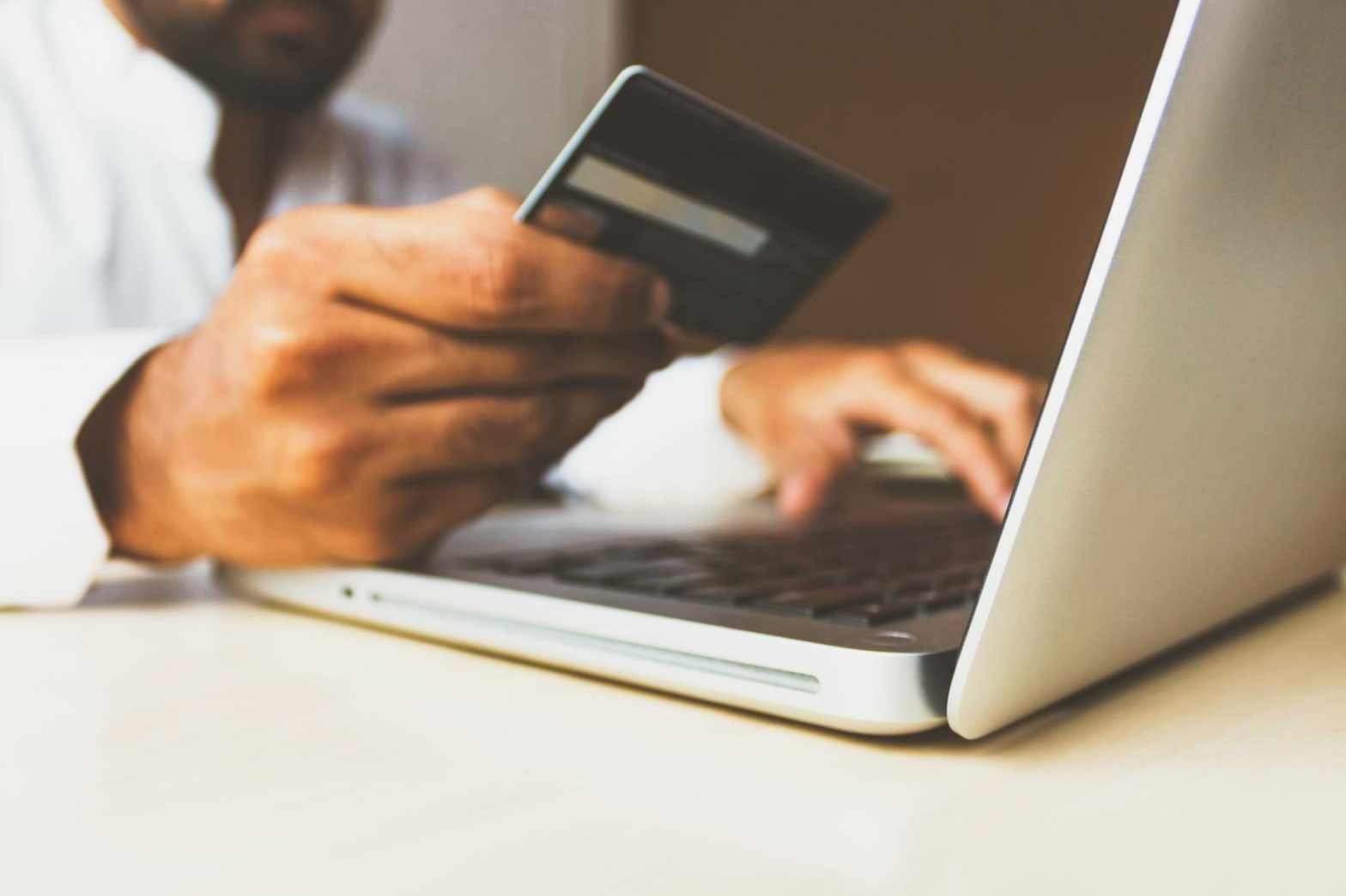A man carefully copies his credit card information into his laptop, likely making an online purchase