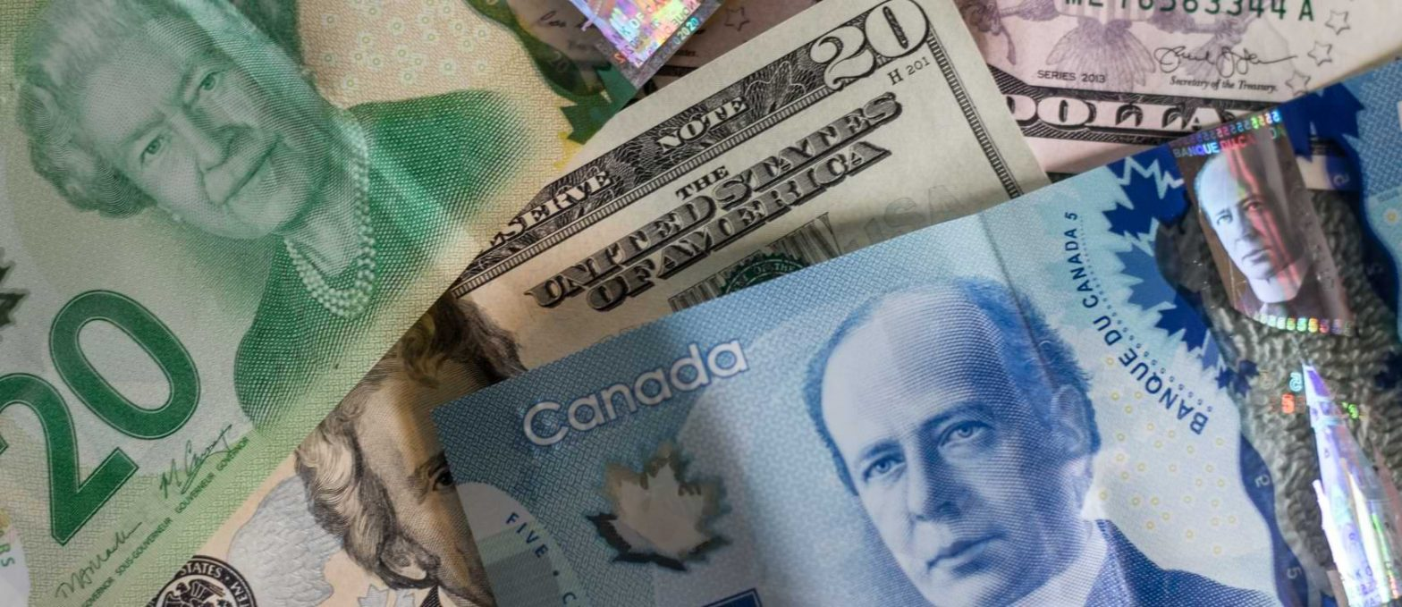 A twenty dollar and five dollar Canadian banknote cover up an American ten dollar bill.
