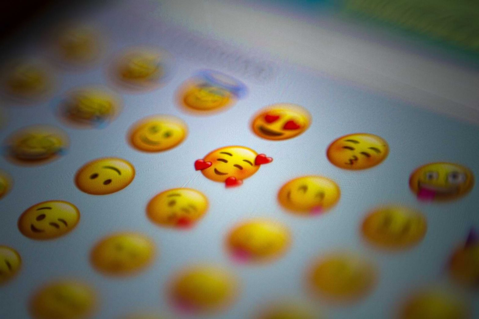 A closeup shot of a phone screen shows a handful of smiling Yellow Emojis