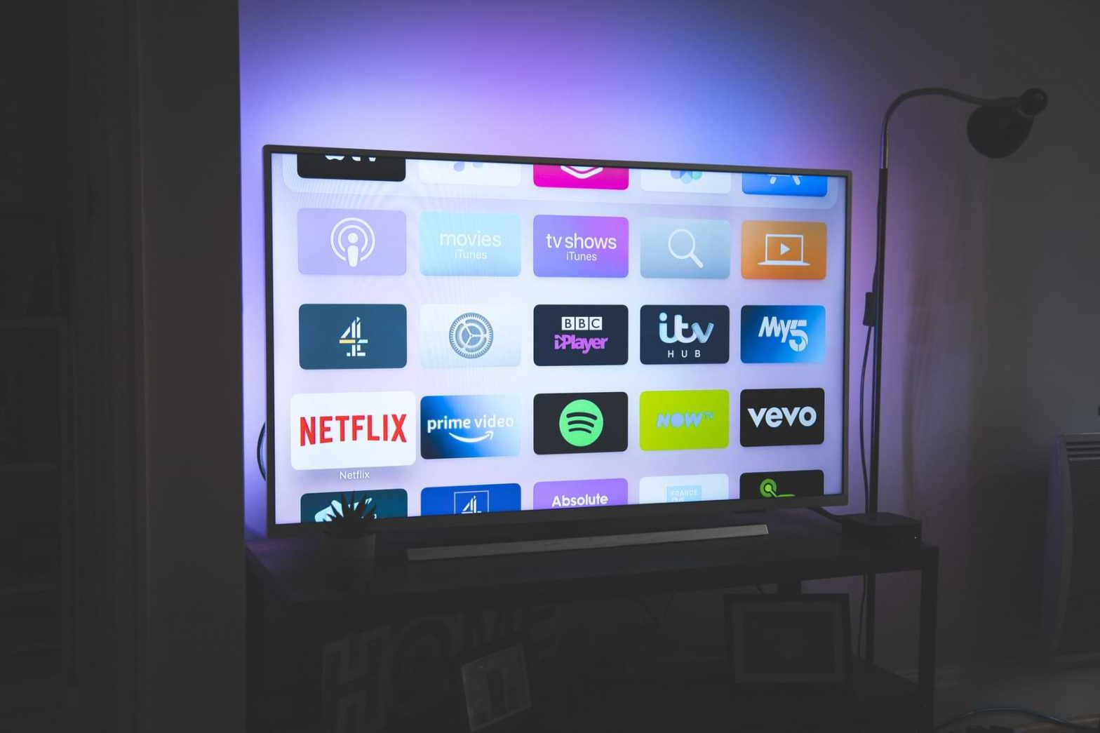 A Smart TV displays various apps like Netflix, Spotify, iTV Hub and more.