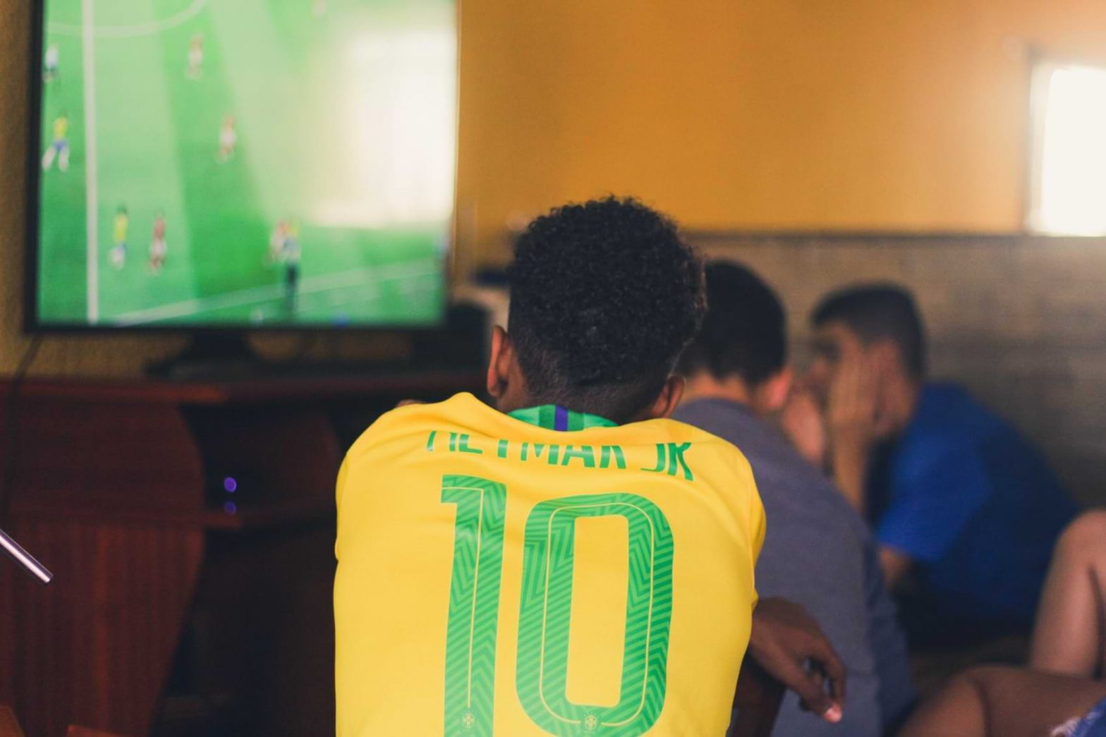A soccer fan wearing a jersey sits in front of his TV and anxiously watches the game