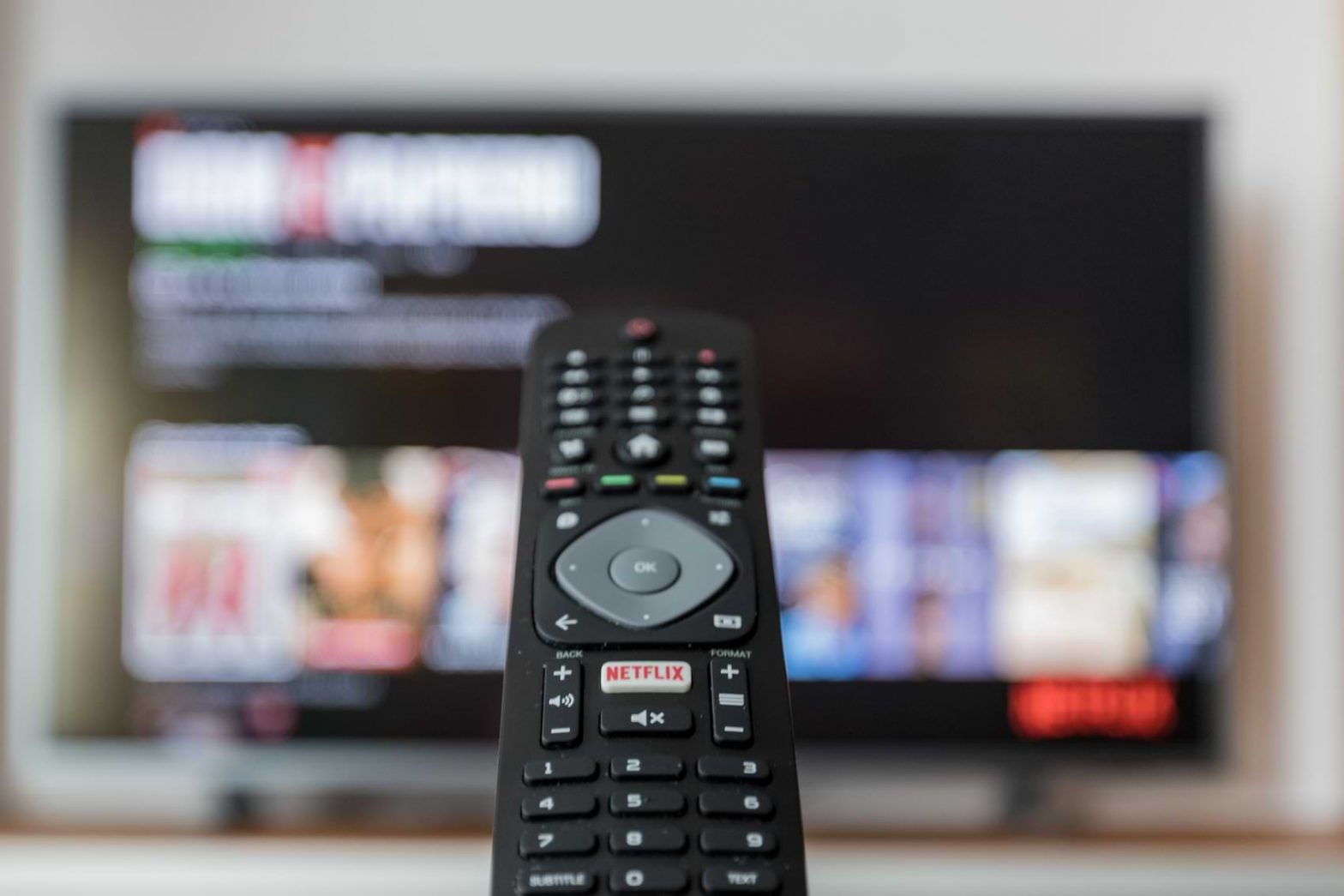 A remote control pointed at a television, searching through the content stored by its HD recorder.
