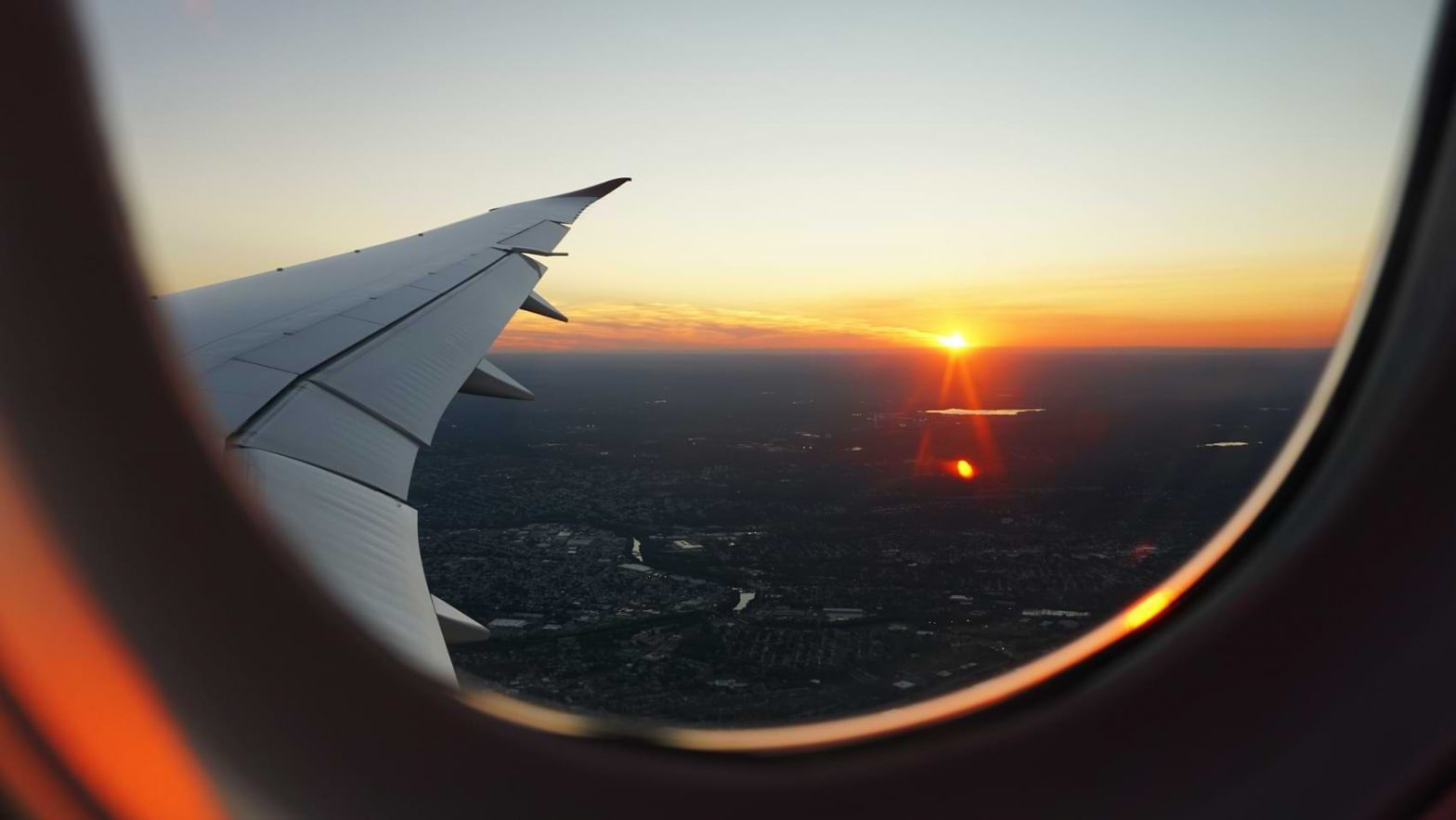 A sunset can be seen lighting up the skyline from the view of an airplane passenger seat.
