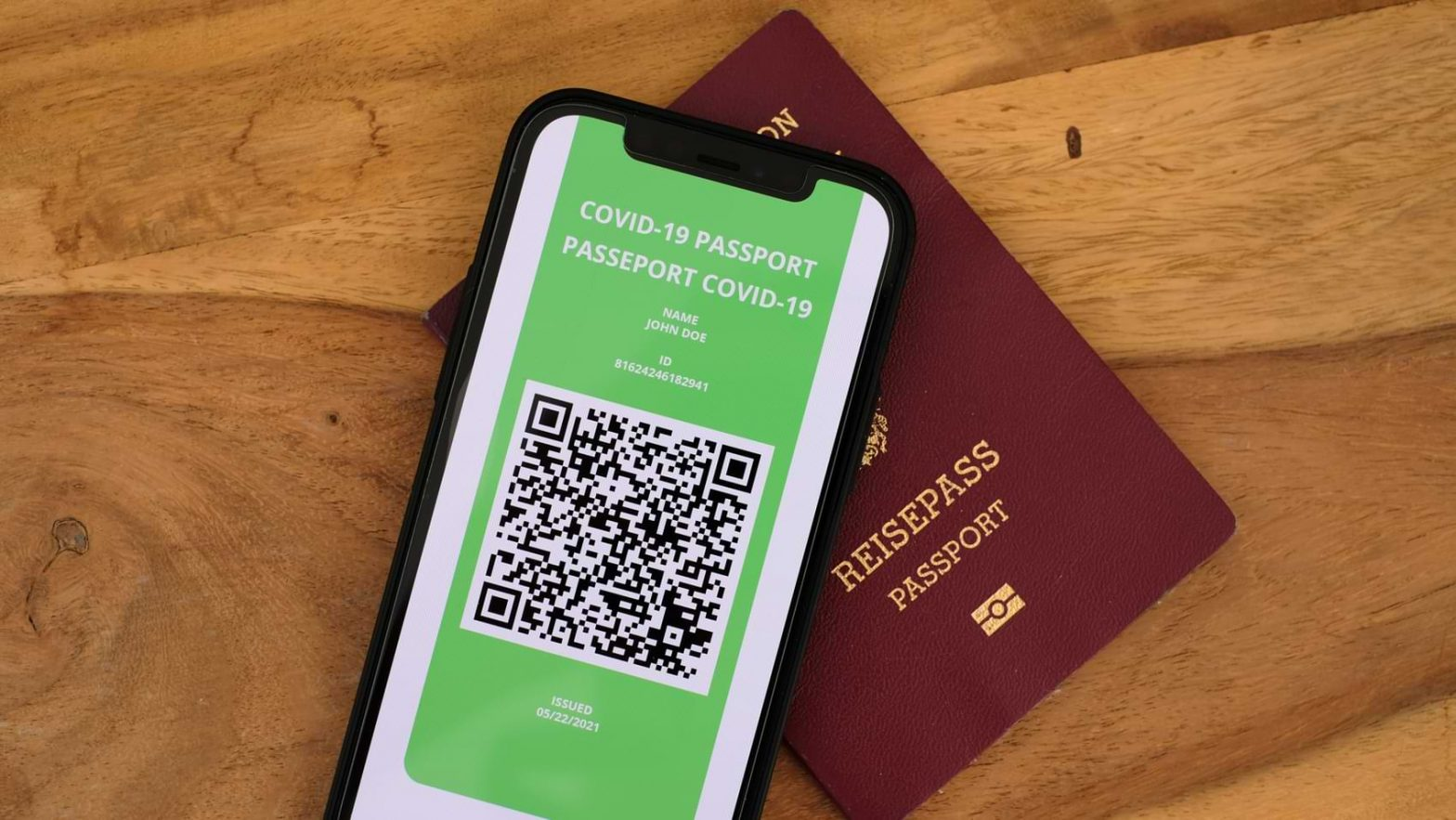 A physical passport next to a COVID-19 passport app on a smartphone.