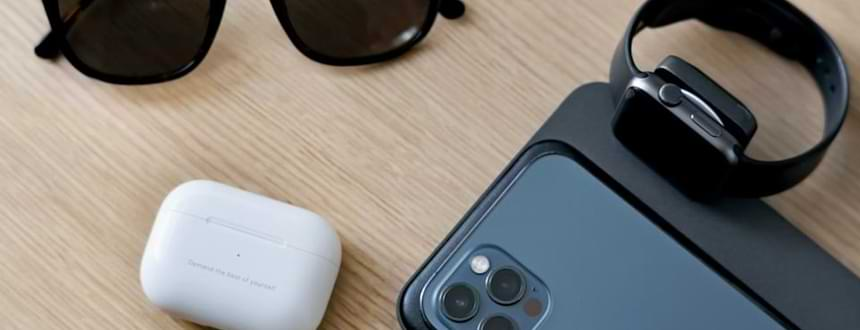 An iPhone next to AirPods and an Apple Watch, two of the best mobile phone accessories for iPhone users.