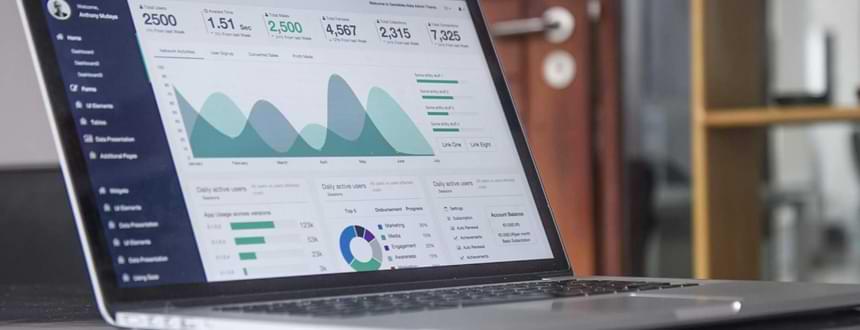 un ordinateur portable posée sur une table avec des statistiques sur l'écran pour savoir Qu'est-ce qu'une bonne vitesse Internet ?