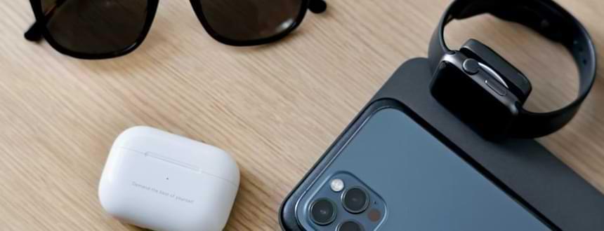 Un iPhone à côté d'AirPods et d'une Apple Watch, un lot d'accessoire cellulaire pour les utilisateurs d'iPhone.